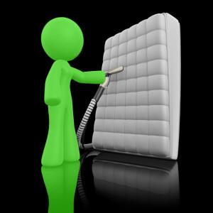 Stylized green cleaning technician vacuums a mattress